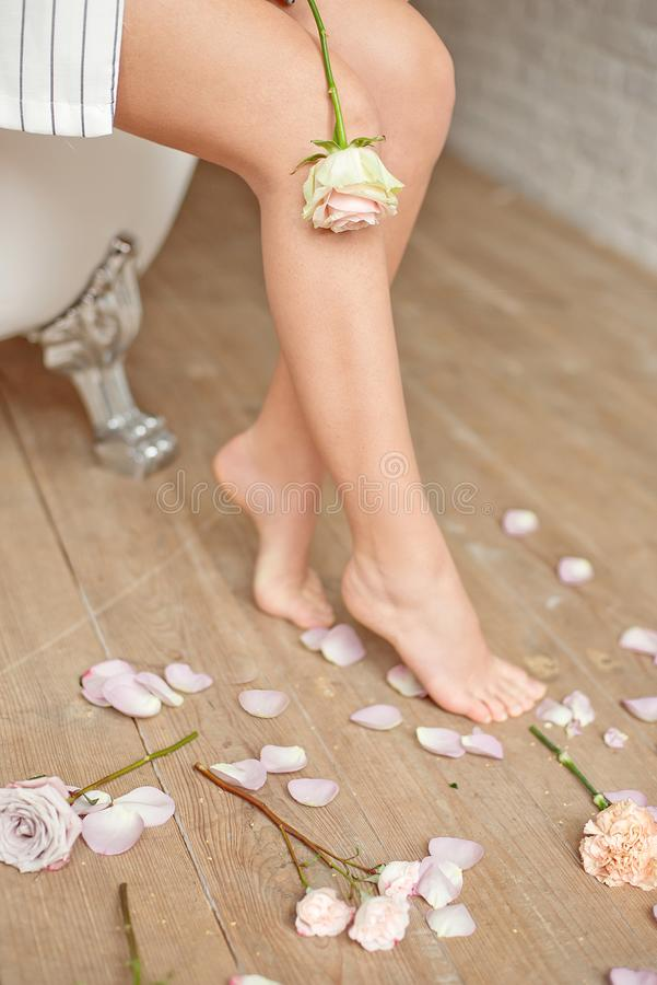 Spa, beauty and wellness bathroom concept with fresh rose petals and flowers scattered around burning candles and the. Graceful barefoot legs of a young woman stock image