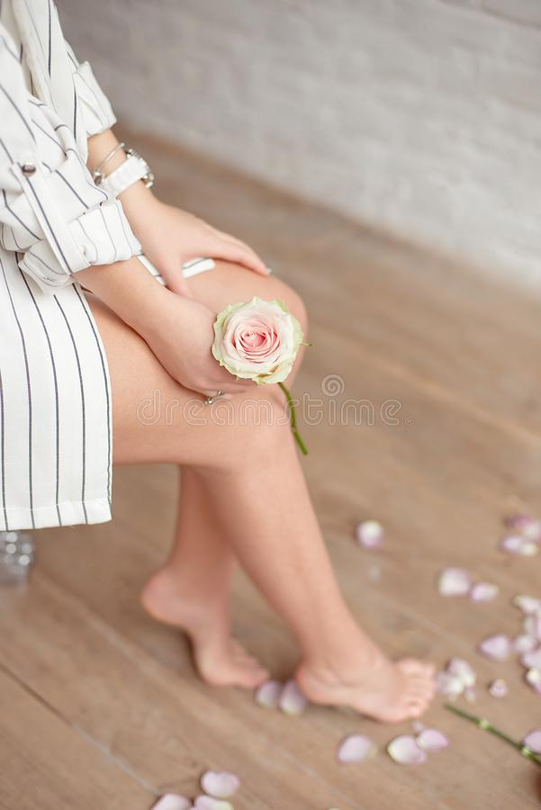 Spa, beauty and wellness bathroom concept with fresh rose petals and flowers scattered around burning candles and the. Graceful barefoot legs of a young woman stock photo