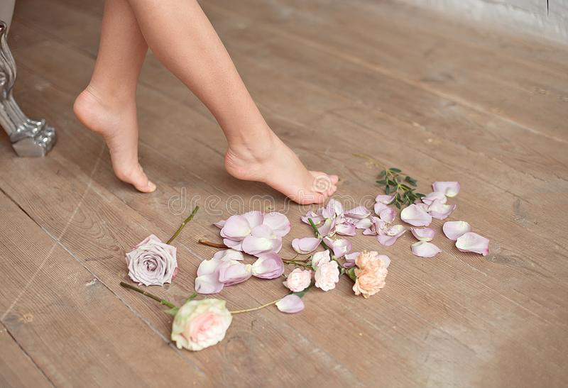 Spa, beauty and wellness bathroom concept with fresh rose petals and flowers scattered around burning candles and the. Graceful barefoot legs of a young woman royalty free stock photos