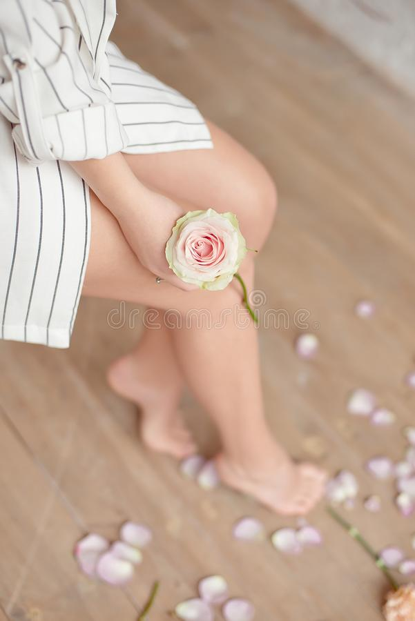 Spa, beauty and wellness bathroom concept with fresh rose petals and flowers scattered around burning candles and the. Graceful barefoot legs of a young woman stock photos