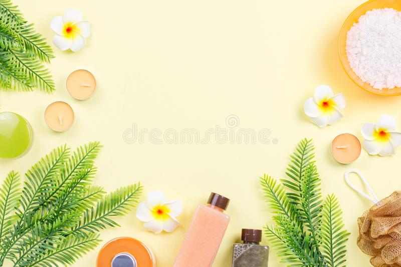 Spa and body care products flat lay. Body scrub, bath salt, moisturizing lotion, candles and leaves on wooden background royalty free stock photography
