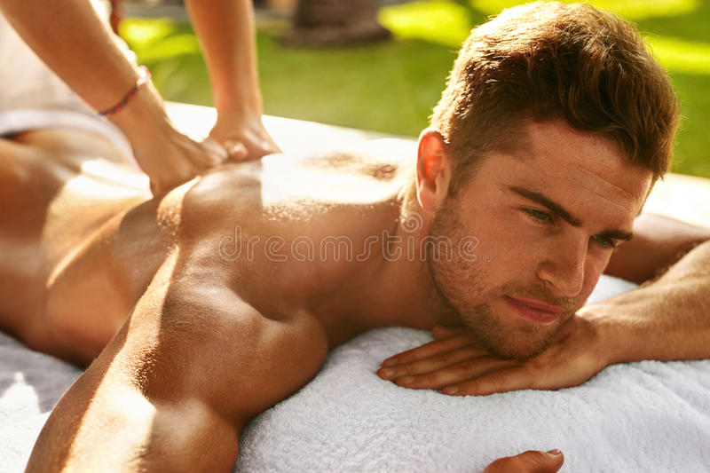 Spa Body Massage. Man Enjoying Relaxing Back Massage Outdoors. Spa Body Massage. Close Up Beautiful Healthy Happy Man Enjoying Relaxing Back Massage In Outdoor stock images