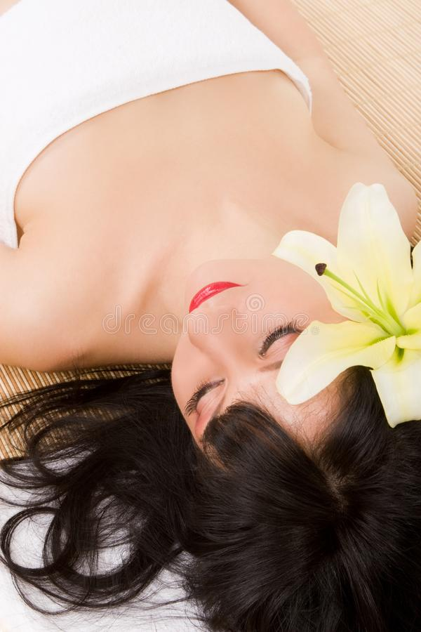 Spa brunette with lily stock photography