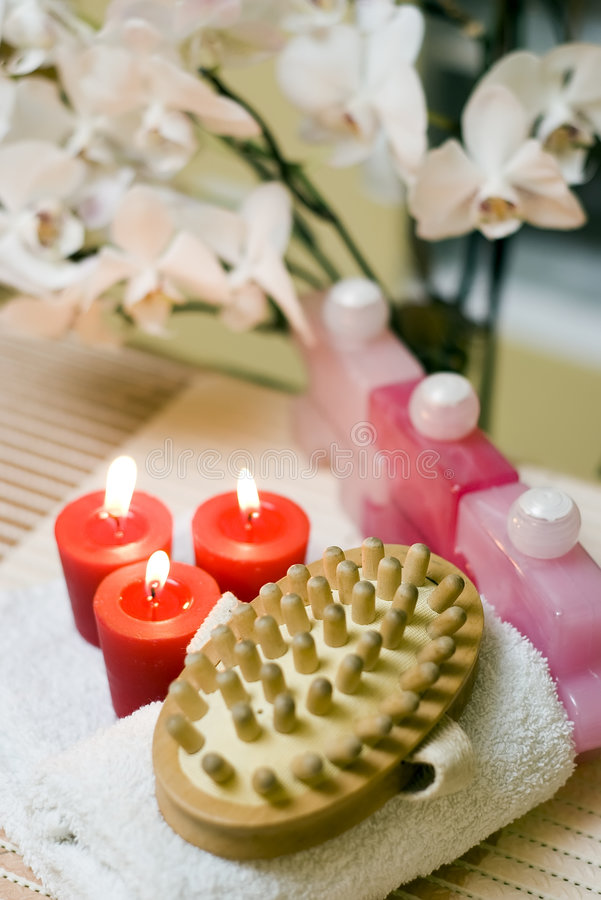 Spa brush composition. A spa massage brush composition with red items and orchid flower in the background royalty free stock photos