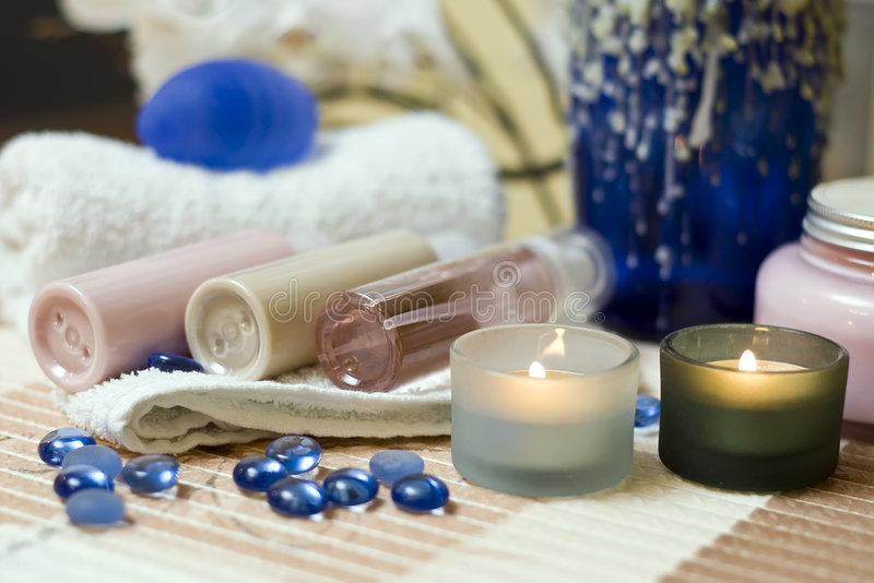 Spa brush and towel. A spa composition, three plastic bottles lying on a towel stock photo