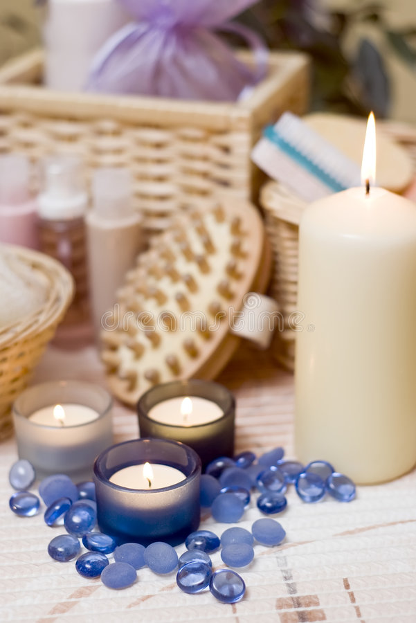 Spa candles composition. A spa composition with bath items and three blue candles in the foreground royalty free stock image