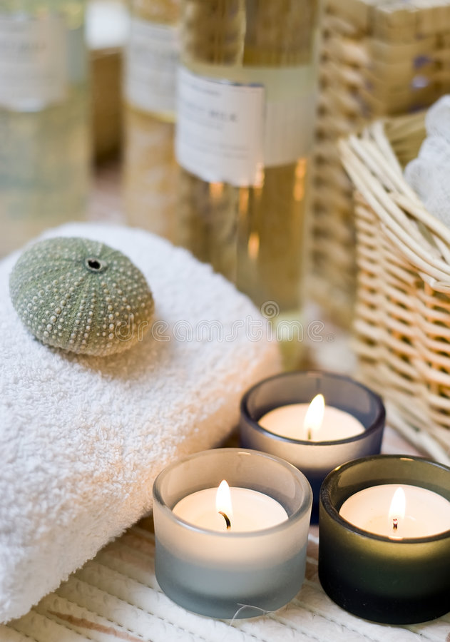 Spa candles composition. Beige spa composition, three small candles in the foreground, cosmetic bottles in the background blurred royalty free stock image