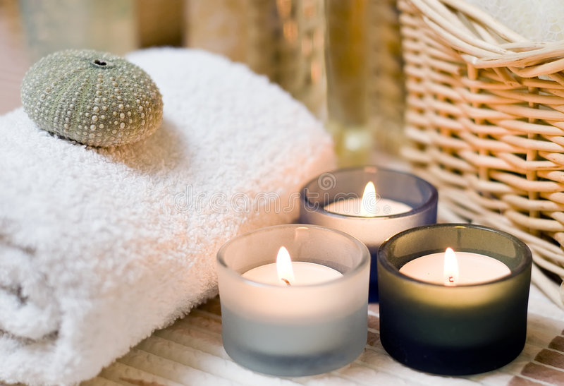 Spa candles composition. Beige spa composition, three small candles in the foreground, cosmetic bottles in the background blurred stock images