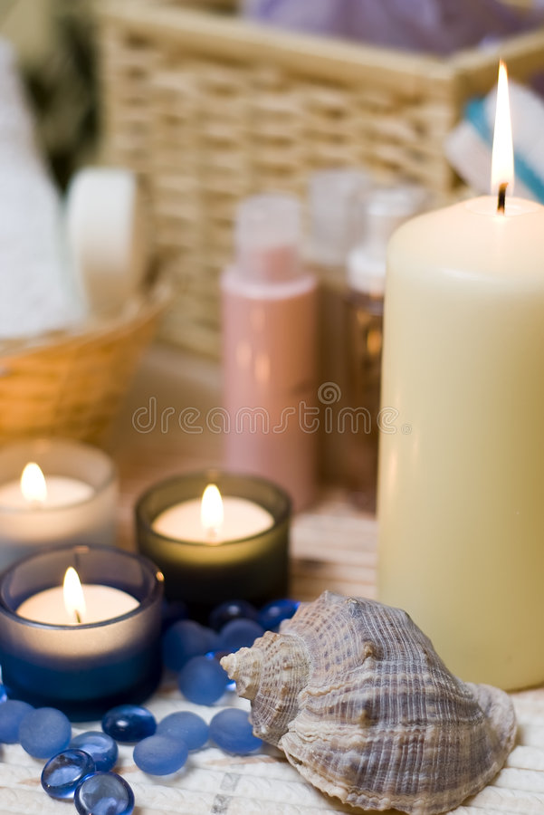 Spa candles and shell. A spa composition with lit candles, a sea shell in the foreground stock photography