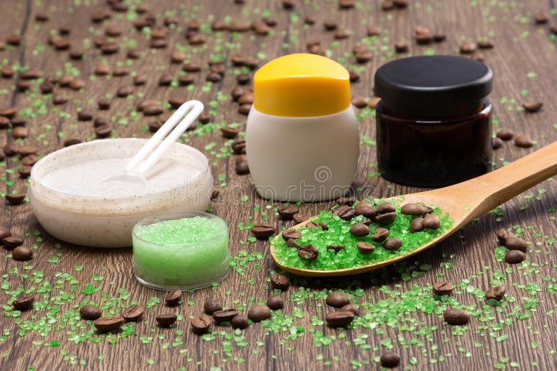 Spa and cellulite busting products on wooden surface. Anti-cellulite cosmetics with caffeine. Close-up of wooden spoon filled with green coarse sea salt and stock images