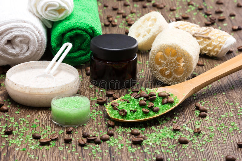 Spa and cellulite busting products on wooden surface. Anti-cellulite cosmetics with caffeine. Wooden spoon with green coarse sea salt and coffee beans, natural stock image