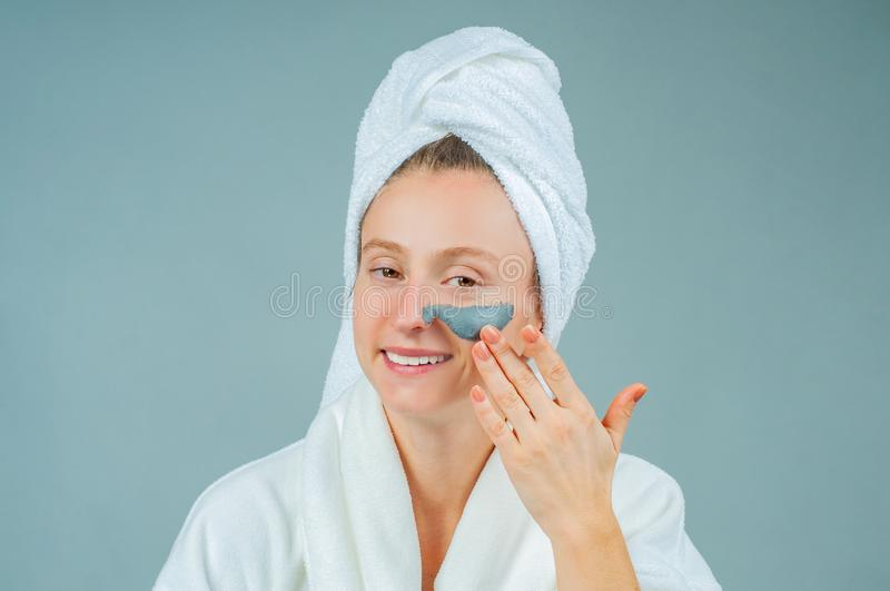 Beautiful young woman applying facial clay mask. Skincare and beauty Concept stock image