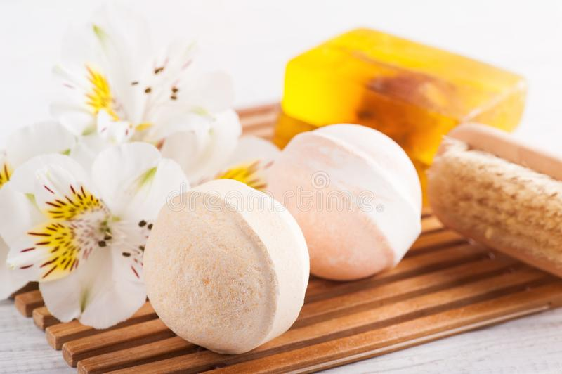 SPA composition with bath bombs. Soap, flowers. White wooden background stock photography