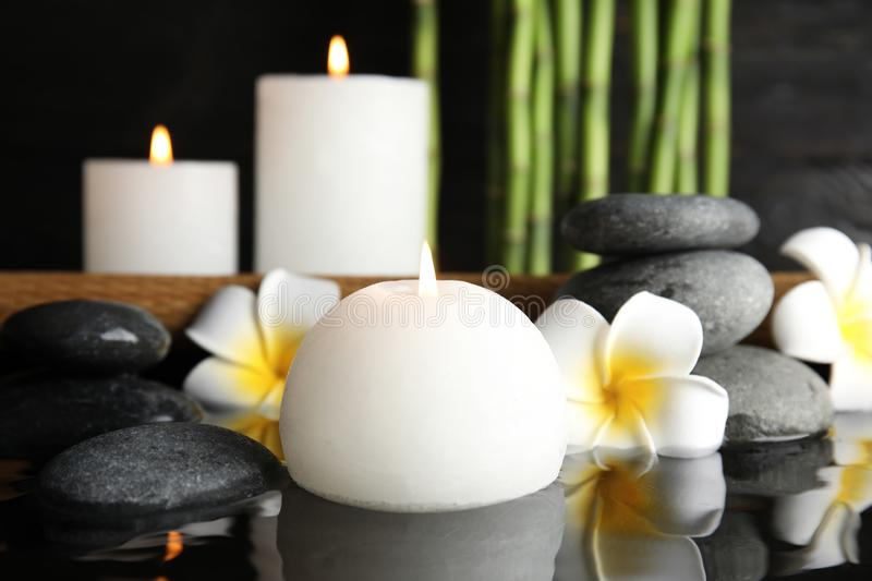 Spa composition with burning candle. In water royalty free stock image
