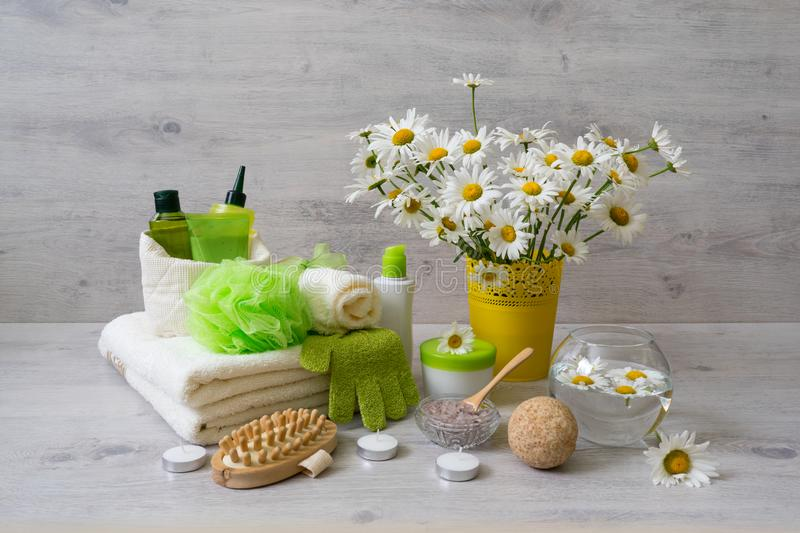 Spa composition with daisy flowers: cosmetic and bath products,. Accessories for massage and peeling on light background. Wellness concept, front view, copy stock photography