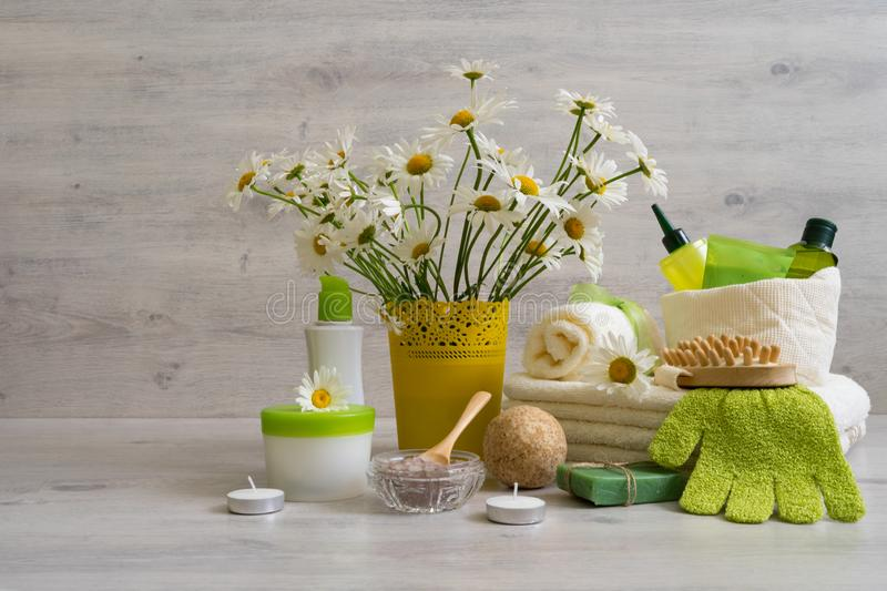 Spa composition with daisy flowers: cosmetic and bath products,. Accessories for massage and peeling on light background. Wellness concept, front view, copy stock photos