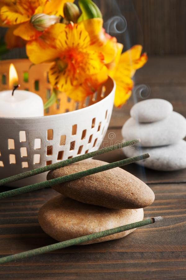SPA composition with aroma sticks. SPA composition with pebbles, aroma sticks, lit candle. Dark wooden background stock image