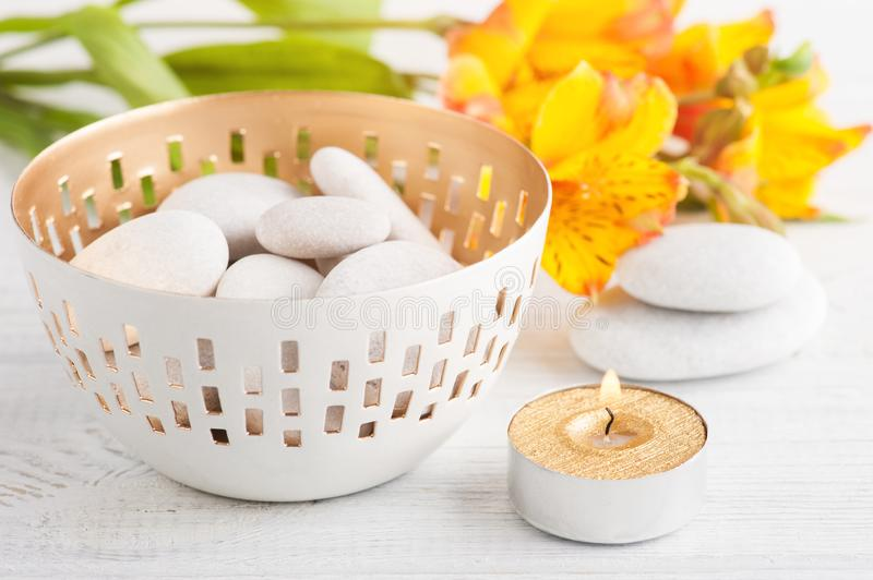 SPA composition with pebbles. Golden lit candle. White wooden background stock photo