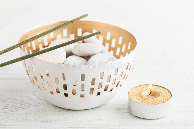 SPA composition with pebbles. Aroma sticks, lit candle. White wooden background stock photo