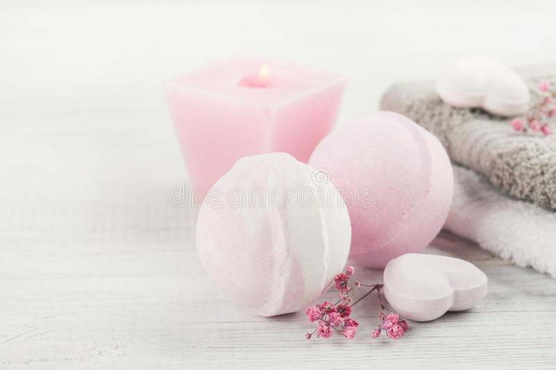 SPA composition with bath bombs. SPA composition with pink bath bombs, heart on white wooden background. Top view, copy space stock images