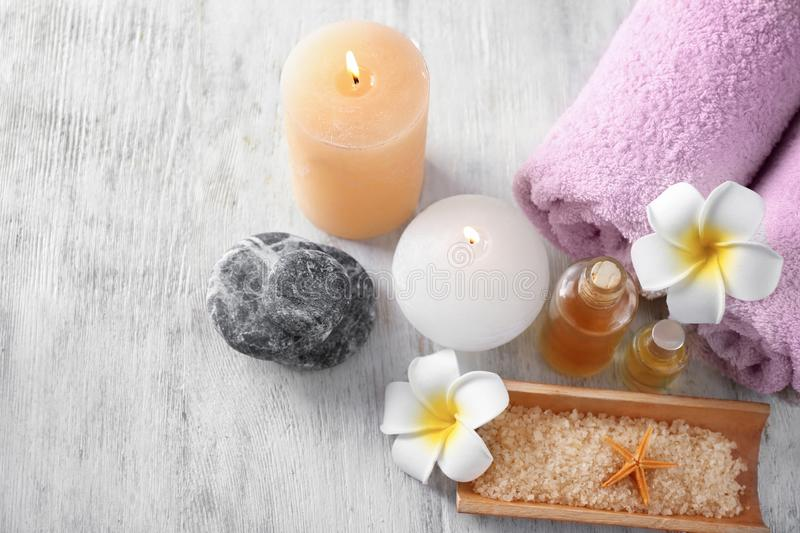 Spa composition with rolled towels, candles and sea salt on wooden background stock photo