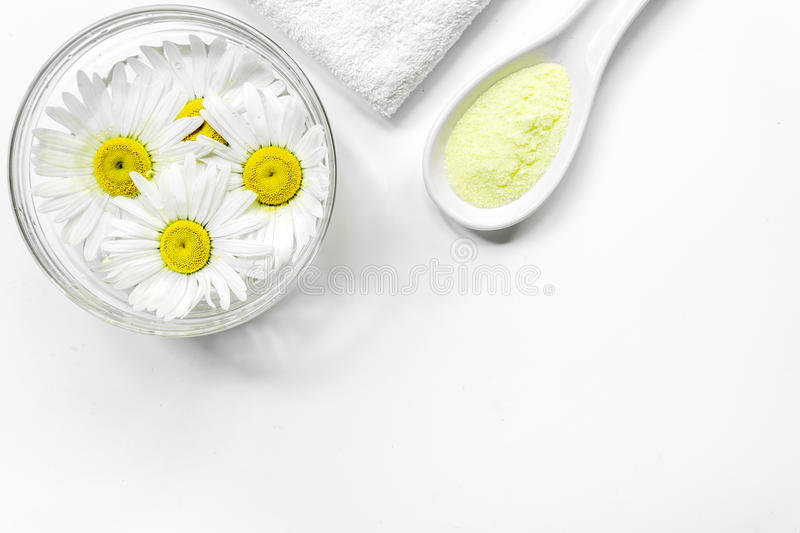 Spa composition with salt, chamomile and towel copyspase top view white background royalty free stock photo