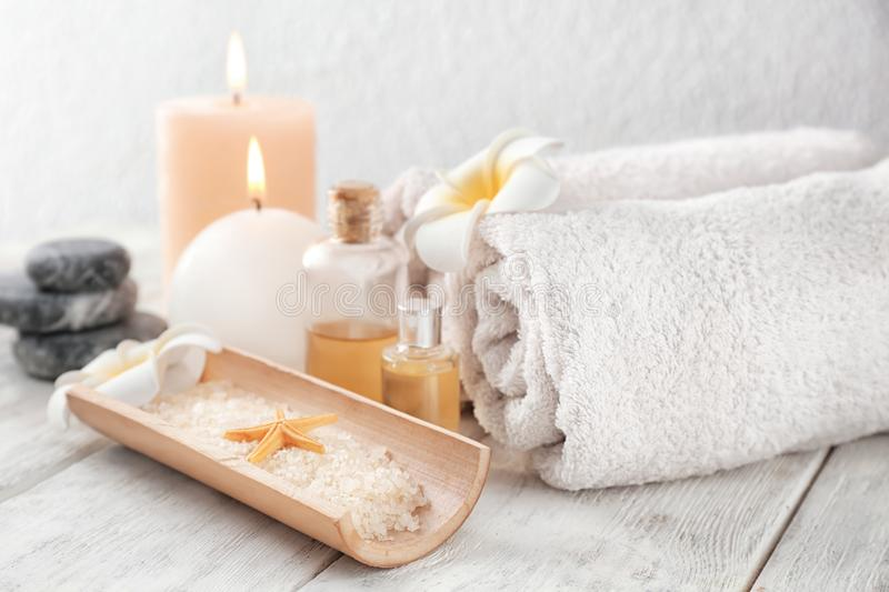 Spa composition with sea salt, candles and rolled towels on light background stock images