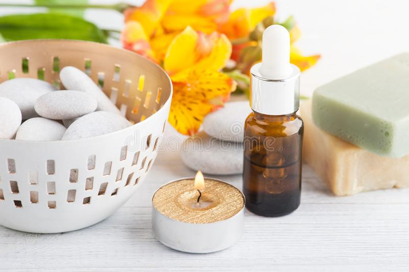 SPA composition with soap. SPA composition with pebbles, soap, lit candle. White wooden background royalty free stock photo