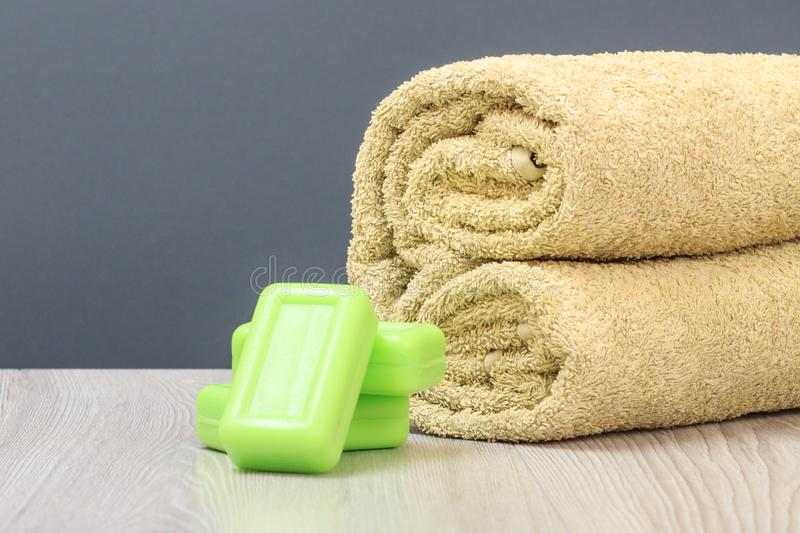 Spa composition with soft terry towel and soap on wooden boards. And gray background royalty free stock photography