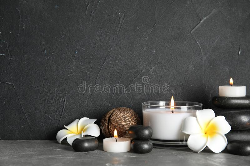 Spa composition with stones and candles on table. Space for text stock image