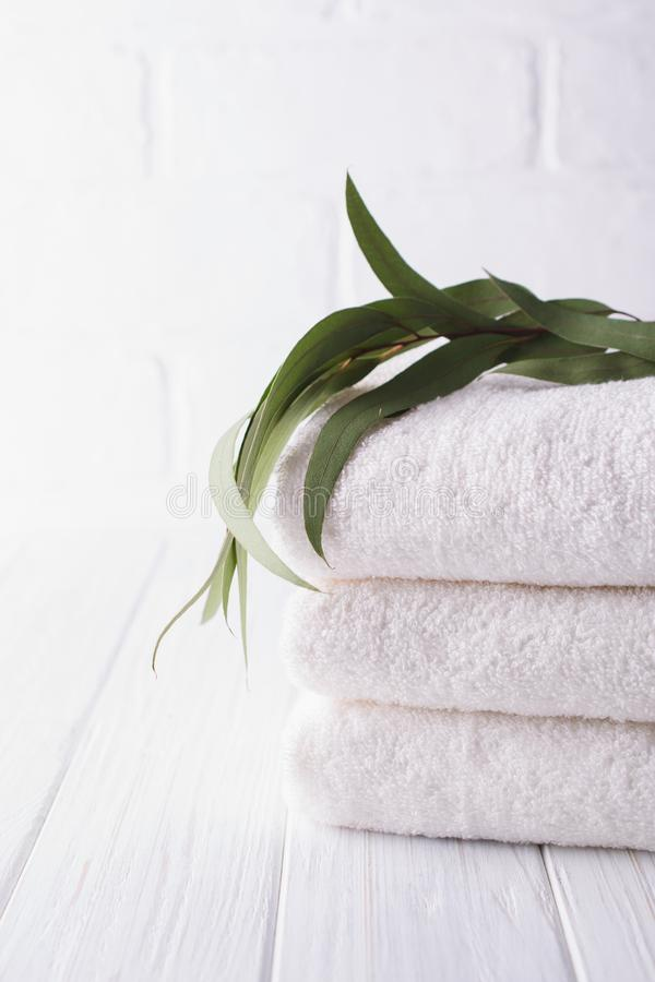 Spa composition on wooden table. Stack of three white fluffy bath towels with eucalyptus branch. stock photo