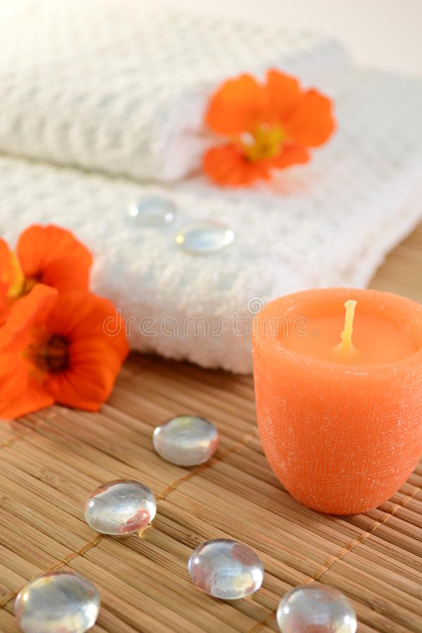 Spa concept. Image of spa concept with candle,towels,orange flowers, and glass stones royalty free stock photography