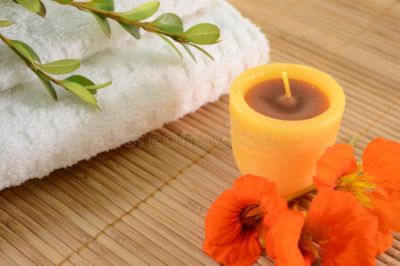 Spa concept. Image of spa concept with candle,towels,orange flowers, and leaves