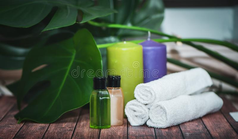 Spa concept, aloe gels and oils, candles. And towels on natural wooden background royalty free stock photography