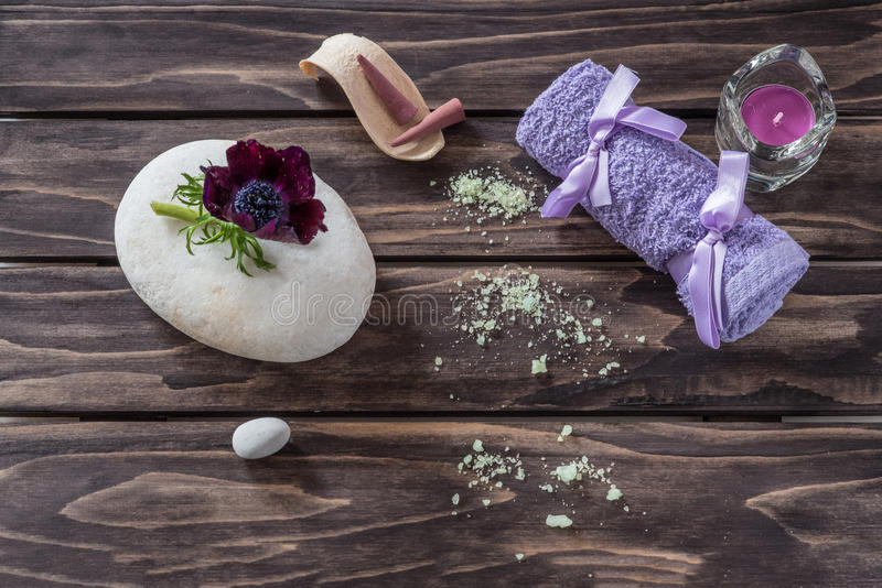 Spa concept. flowers,candles, aromatic salt and bath purple towel royalty free stock photo