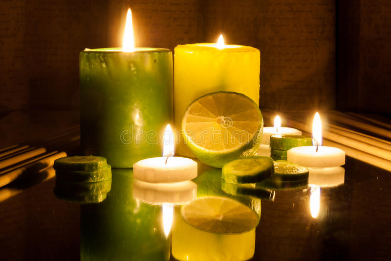 Spa Concept- Green and Yellow lit candles, Slice of lemon. Green and Yellow lit candles, Slice of lemon. Spa concept stock image