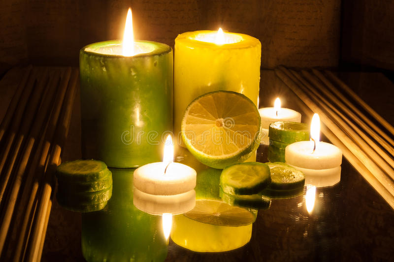 Spa Concept- Green and Yellow lit candles, Slice of lemon. Green and Yellow lit candles, Slice of lemon. Spa concept stock images
