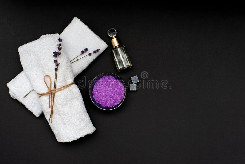Spa concept. Lavender salt for a relaxing bath, aroma oil, white towels and dry lavender flowers on a black background. Aromatherapy Flat lay stock photo