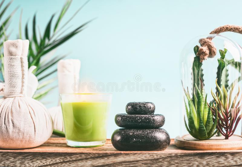 Spa concept with massage equipment: stack of massage stones, aromatherapy candles, herbal stamps setting on wooden table with. Succulent plants at light blue royalty free stock image