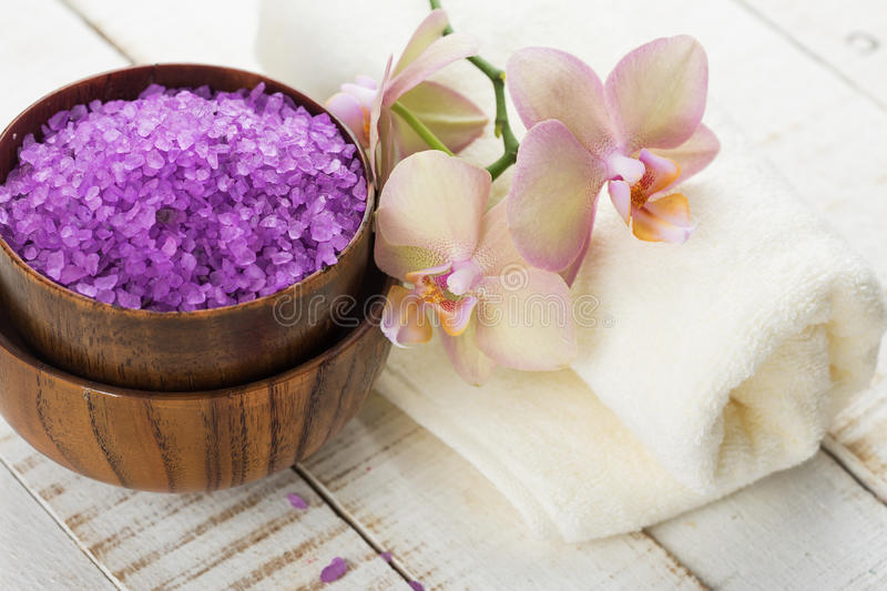 Spa concept. Sea salt in bowl with flowers and towel on white wooden background stock images