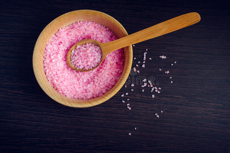Spa concept - sea salt in the bowl. Spa and wellness concept - pink sea salt in the bowl with the wooden spoon on dark wooden background. Aromatherapy concept stock photography