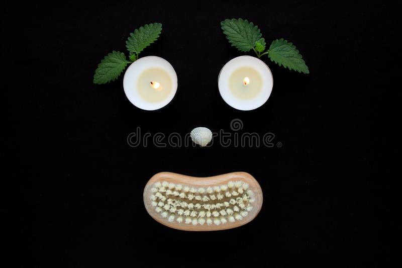 Spa wellness concept, face with eyes candles, a seashell nose and a mouth of a wooden body brush on black background. Spa concept, silhouette of a face with eyes stock images