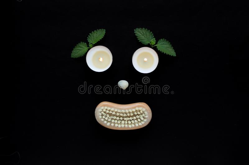 Spa wellness concept, face with eyes candles, a seashell nose and a mouth of a wooden body brush on black background stock photography