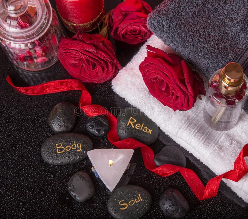 Wellness decoration, Spa concept in Valentine`s Day. Spa concept in Valentine`s Day, red roses, candles in the shape of heart, black therapy stones with the royalty free stock photography
