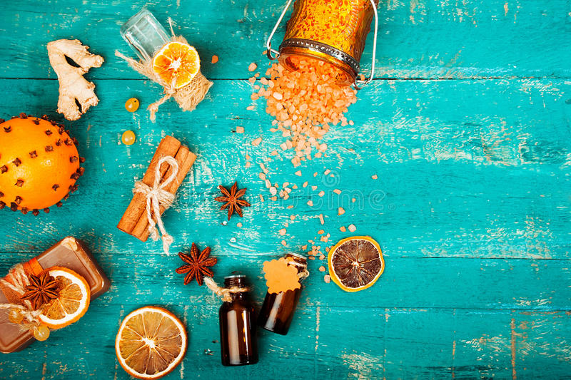 Spa concept on wooden background: Aromatic oils, salt, soap, citrus, cinnamon candles. royalty free stock image