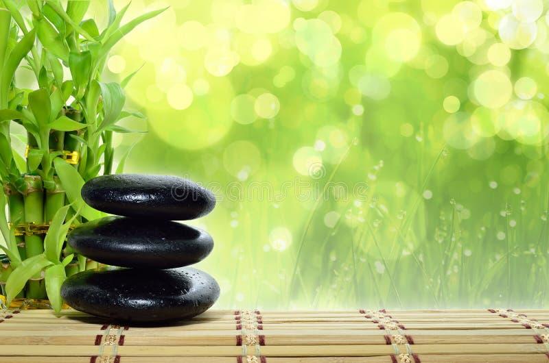 Spa concept zen. Basalt stones with bamboo royalty free stock photos