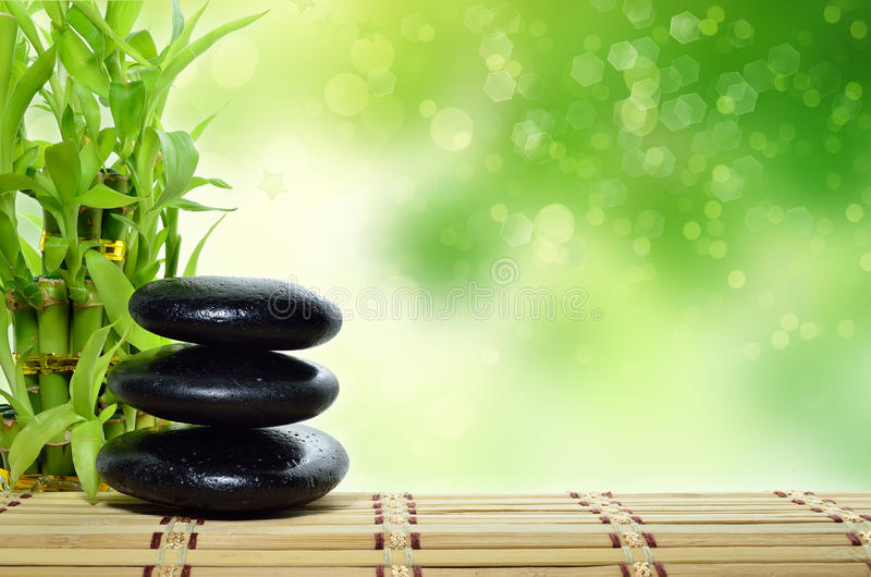 Spa concept zen. Basalt stones with bamboo royalty free stock photography