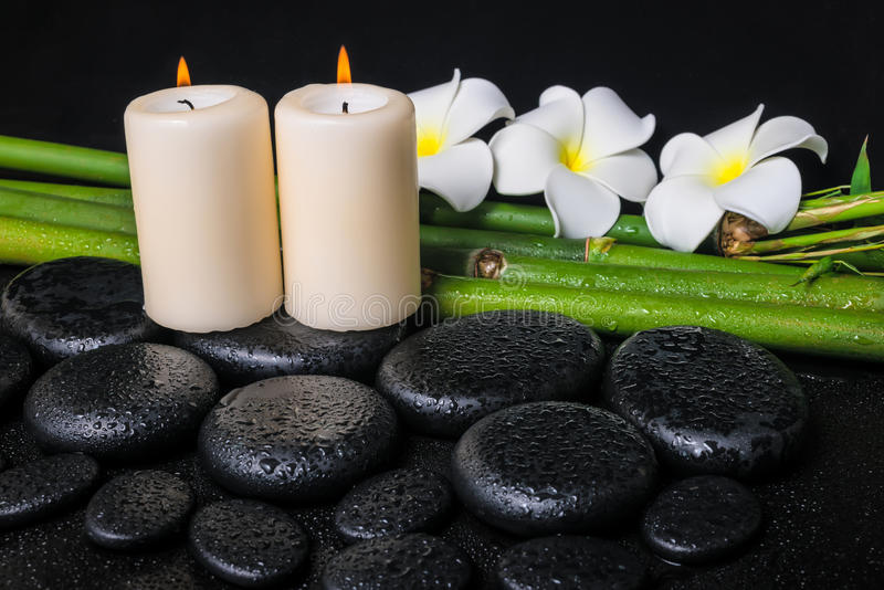 Spa concept of zen basalt stones, three white flower frangipani. Candles and natural bamboo with drops, closeup royalty free stock photos
