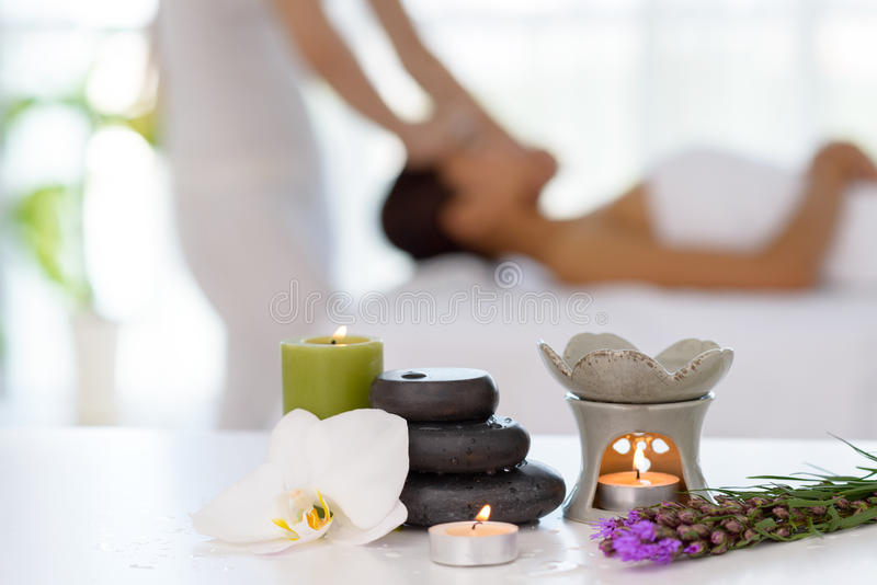 Spa concept. Zen stones, candles and flowers on the background of woman receiving treatment stock photos
