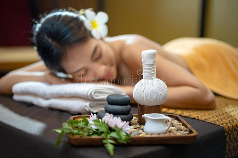 Spa concept, Zen stones, Candles and flowers on the background of woman receiving treatment, Young beautiful woman in spa. Environment. Blurred face royalty free stock photos